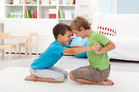 Two happy boys wrestling in the kids room photo