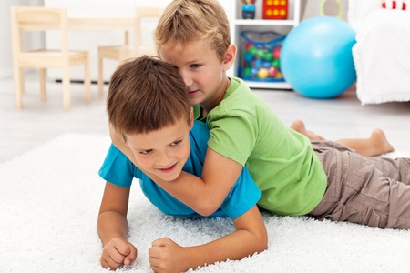 Kids wrestling and playing on the floor at home