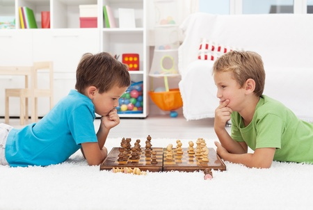 board games: Two boys playing chess laying on the floor and thinking hard