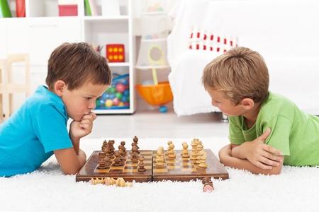 jugando ajedrez: Niños jugando al ajedrez tirado en el suelo y pensar intensamente Foto de archivo