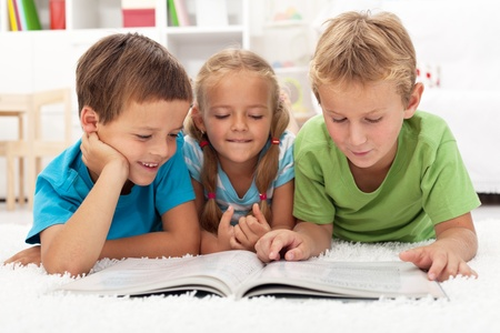 Kids practice reading together enjoying a book laying on the floor Stock Photo - 10744881