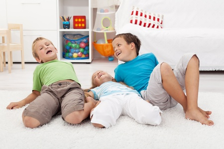 Three happy kids playing and having fun on the floor laughing photo