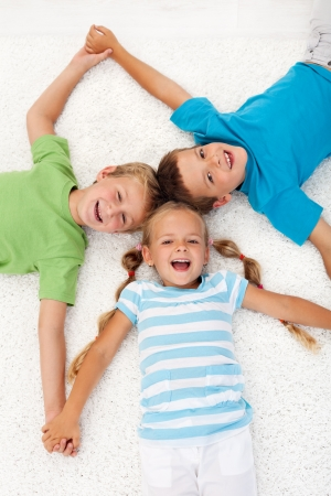sibling: Happy healthy laughing kids laying on the floor Stock Photo