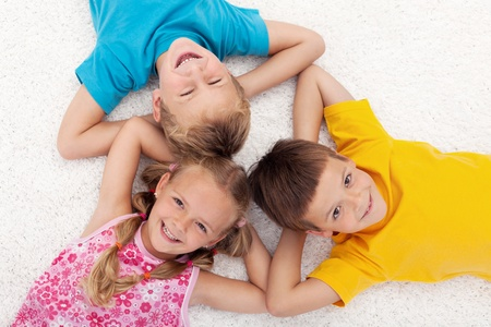 beautiful boy: Three happy kids laying on the floor in circle laughing