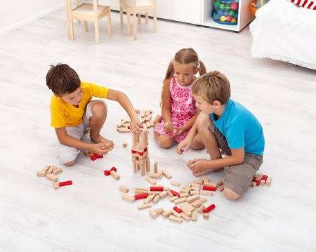 kids activities: Three kids playing with wooden blocks in their room - top view Stock Photo