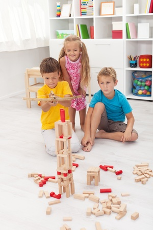 Kids playing with a bow and arrow - shooting a wooden blocks tower photo