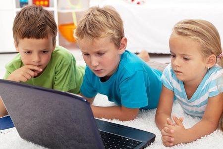 Serious and focused kids looking at laptop computer laying on the floor photo