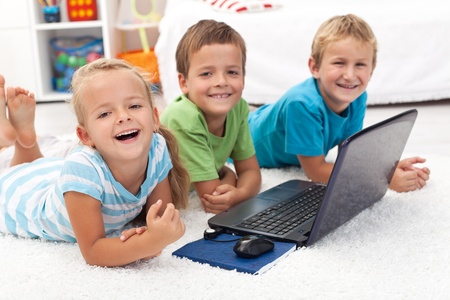 Happy healthy kids with laptop computer laying on the floor Stock Photo - 10744868