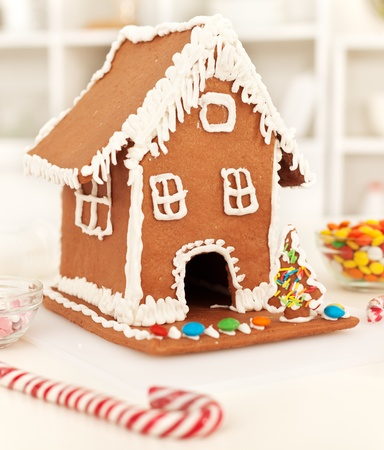 Christmas time in the kitchen with gingerbread house and candy stick photo