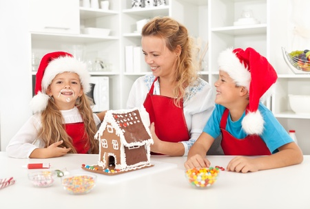 Family having fun in the kitchen while decorating a gingerbread cookie house Stock Photo - 10744866