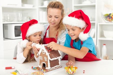 decoracion de pasteles: Familia feliz en el tiempo de Navidad que adorna una casa de jengibre en la cocina