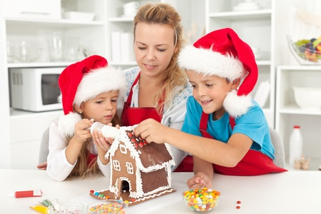 holiday cooking: Happy family at christmas time decorating a gingerbread house in the kitchen Stock Photo