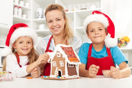 Happy christmas family in the kitchen decorating a gingerbread house photo