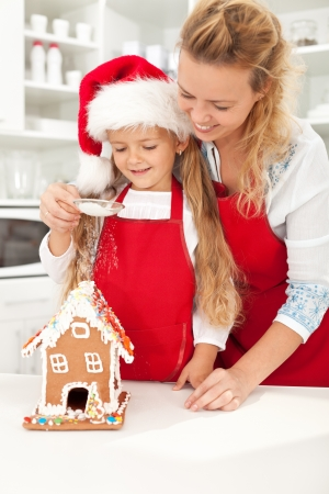 Happy christmas people making gingerbread house Stock Photo - 10744887