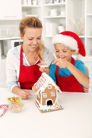 disperse: Final touches on the gingerbread house - people at christmas time in the kitchen Stock Photo