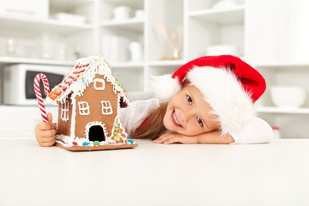 Happy girl preparing for christmas with gingerbread house photo
