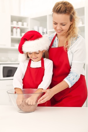 Preparing the christmas cookie dough - happy girls in the kitchen Stock Photo - 10744861