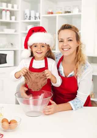 Happy woman and little girl at christmas time in the kitchen preparing cookies Stock Photo - 10744896