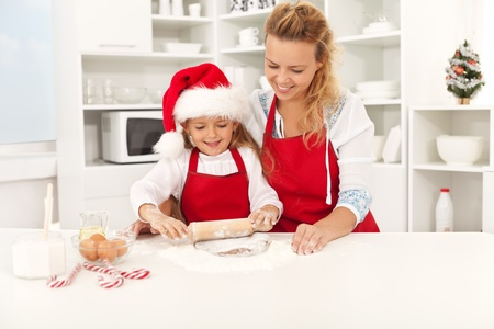 Happy woman and girl stretching the christmas cookie dough together Imagens