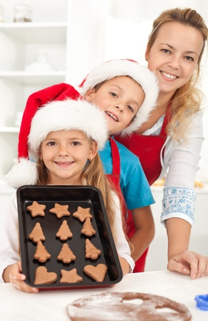 Happy family at christmas time baking gingerbread cookies