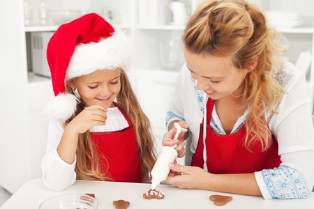 Happy christmas people decorating the gingerbread cookies Stock Photo - 10744878