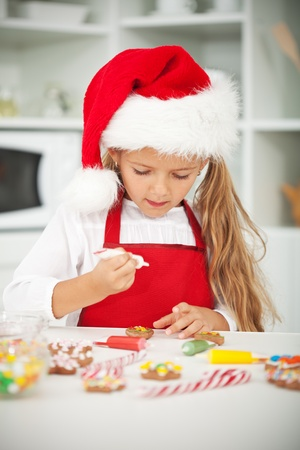 Little girl at christmas time in the kitchen decorating the cookies Stock Photo - 10744852