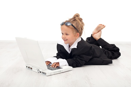 business roles: Little girl playing businesswoman with a laptop on the floor Stock Photo