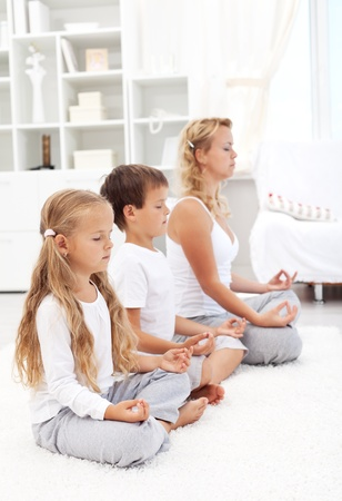 Family sitting in a row meditating - happy, healthy and balanced life concept photo