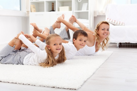 physical activity: Family doing gymnastic exercises at home - healthy life education