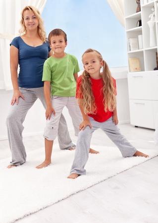 educacion fisica: Personas que hacen ejercicio en casa - mujer con sus hijos se extiende