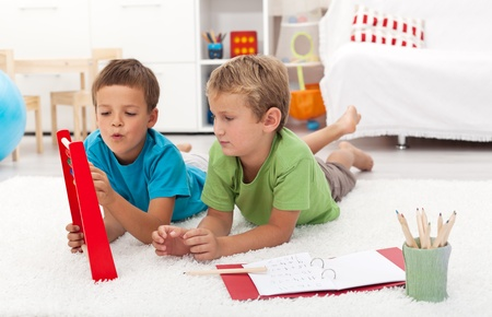 Elementary school boys doing math exercises at home - laying on the floor photo