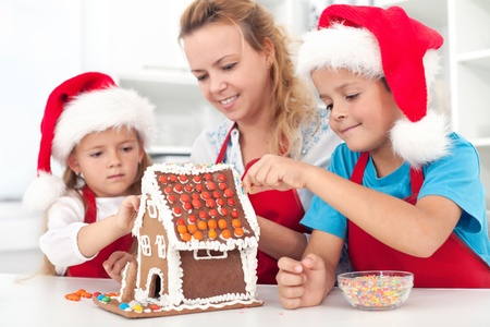 Family preparing a gingerbread cookie house at christmas time photo