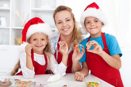 Happy family making and decorating christmas cookies photo