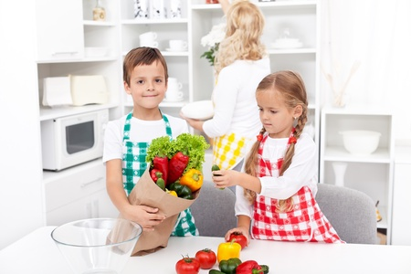 Kids with aprons unpacking groceries from paper bag in the kitchen photo