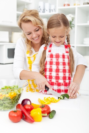 slicing: Mother and little girl slicing vegetables in the kitchen preparing a salad Stock Photo