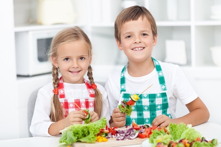 kitchen apron: Happy healthy kids preparing a vegetables meal in the kitchen Stock Photo