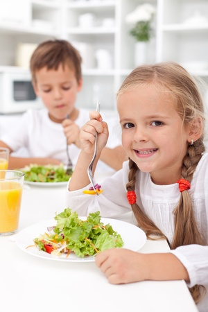 beautiful salad: Kids in the kitchen eating healthy vegetables