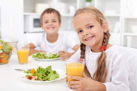 kids eating healthy: Kids eating a healthy meal in the kitchen