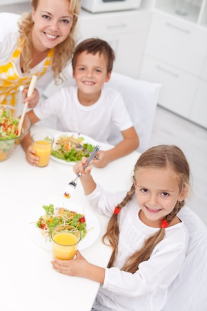 Morning in the kitchen - woman and kids eating healthy breakfast Stock Photo - 10986747