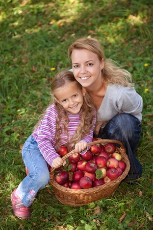 Woman and little girl with a basket of freshly picked apples photo