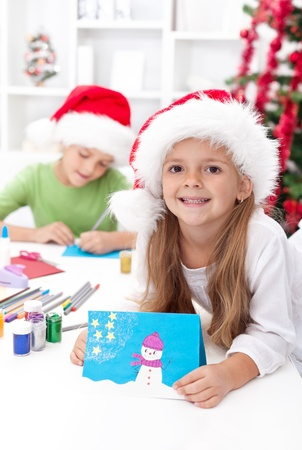 xmas crafts: Children making christmas greeting cards wearing santa hats Stock Photo