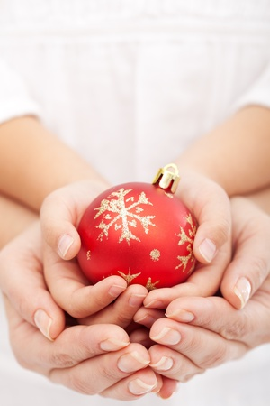 Christmas together concept with child and adult hands holding bauble