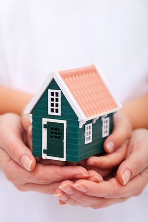 protect home: Protect your home - hands holding small house - insurance concept