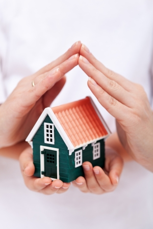Protect your home - small house shielded with hands Stock Photo - 11411237