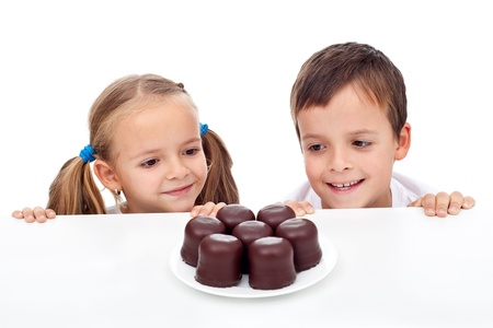 eating chocolate: Kids craving sweets, happy to found some Stock Photo