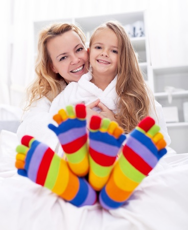Happy girl and woman at home after bath wearing colorful socks photo