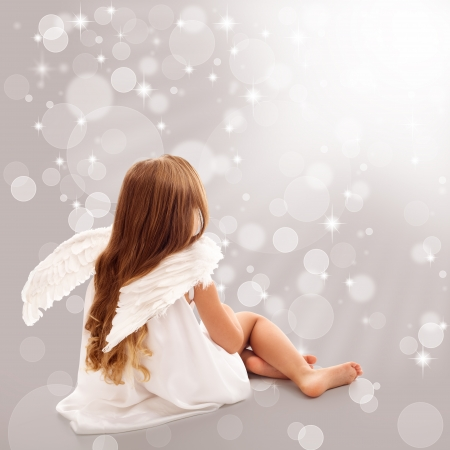 angel girl: Little angel thinking in divine light while sitting Stock Photo