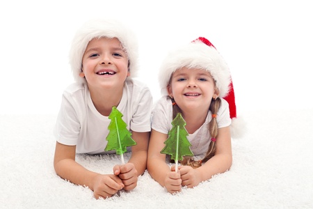 Kids with candy at christmas time smiling on the floor photo