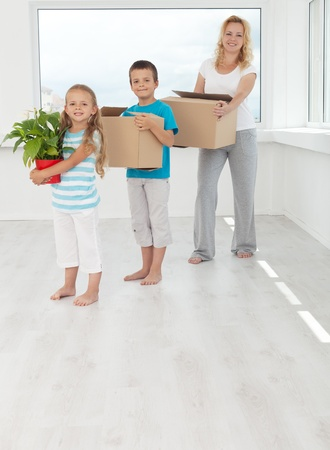 Happy people in their new home with boxes and potted plant photo