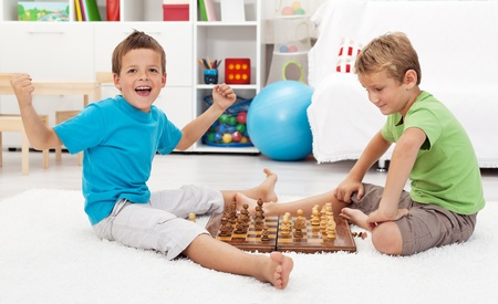 Boy wins chess game with a few moves cheering photo